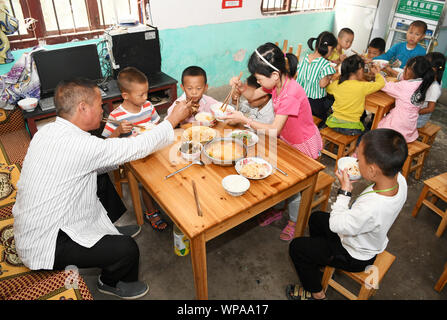 (190908) -- GUIYANG, Sept. 8, 2019 (Xinhua) -- Jiang Tongying has lunch with children at Hua'ao primary school in Jianhe County of Qiandongnan Miao and Dong Autonomous Prefecture, southwest China's Guizhou Province, Sept. 6, 2019. Jiang Tongying is a 56-year-old teacher of Dong ethnic group in Hua'ao primary school where he has been working since1982. Though some young teachers joined him to teach, they eventually left because of tough living condition or inconvenient transportation.    From 2013 on, the school saw less and less number of pupils as locals went out as migrant workers or relocat - Stock Photo