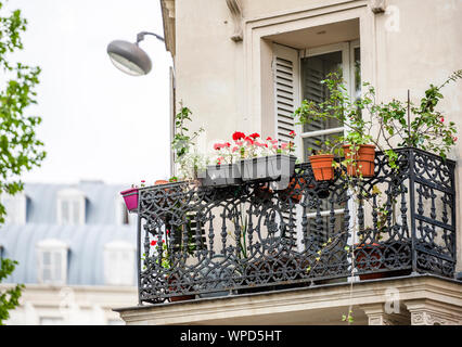 Residential multi-storey apartments house with wooden shutters and metal balcony with flowers in flowerpots and street lamp on the wall located on one - Stock Photo