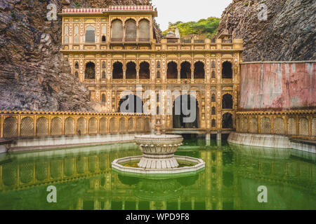 Monkey temple (galtaji) with pilgrims bathe in Jaipur, India. - Stock Photo