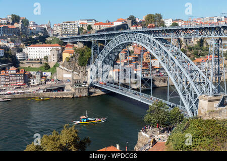Porto, Portugal.  Dom Luis I bridge crossing the Douro river and linking Vila Nova de Gaia, bottom, and Porto, top.  The boats, called rabelos, once t - Stock Photo