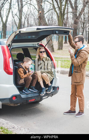 young family packing for car travel. putting bags into trunk - Stock Photo