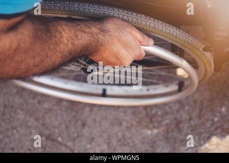 Close up. Disabled Man on Wheelchair in park. Disabled Young Man. Man on Wheelchair. Recovery and Healthcare Concepts. Teamwork in Office. Young Worke - Stock Photo