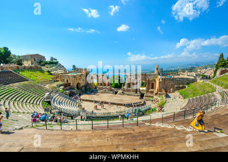 A woman walks up the ancient stairs at the Greek Theatre in Taormina, Italy on the Italian island of Sicily. - Stock Photo