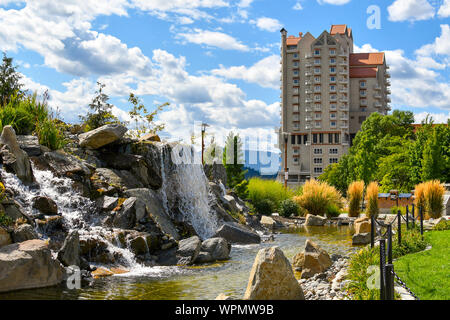 A large pond with waterfall inside the public McEuen Park near resorts and Tubbs Hill in the lakefront town of Coeur d'Alene, Idaho. - Stock Photo
