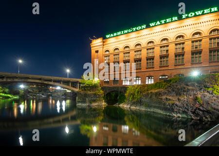 The Washington Water and Power building shines above the Spokane River and Dam near Riverfront Park at night in Spokane, Washington, USA - Stock Photo
