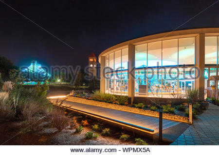 The illuminated Looff Carousel shines with the newly refurbished Spokane Pavilion in the distance in Spokane Washington's Riverfront Park - Stock Photo