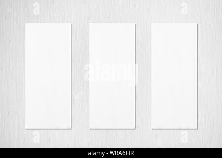 Three empty white vertical rectangle menu mockups with soft shadows on neutral light grey textured wall background. Flat lay, top view - Stock Photo