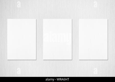 Three empty white vertical rectangle poster or card mockups with soft shadows on neutral light grey textured background. Flat lay, top view - Stock Photo