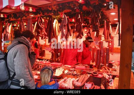 Market stall on a christmas market in Potsdam, selling sausages in all variations. Buyer and seller. Germany, Europe. - Stock Photo