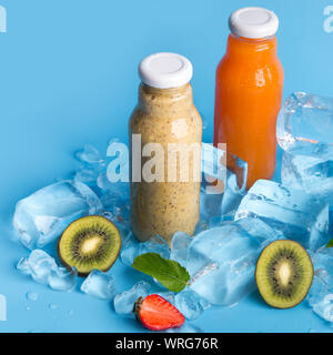 Close up of summer fresh cocktails with fruits and ice on blue - Stock Photo