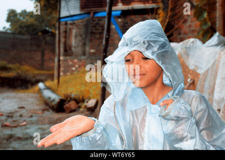 A indian boy wearing rainbows in wet water, village view - Stock Photo