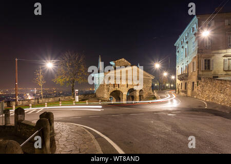 View of the city of Bergamo from Porta San Giacomo old city doors in Upper Town (Città Alta) at night. Bergamo, Lombardy, Italy. - Stock Photo