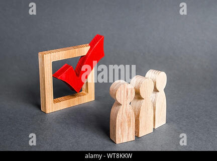 People figurines and a checkbox for voting in democratic elections. Lobbying interests, voter bribery, and rigging presidency or parliamentary electio - Stock Photo