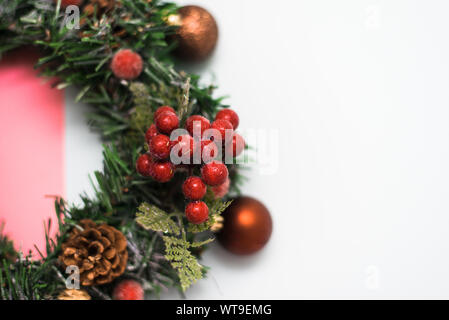 Christmas wreath made of artificial Christmas tree branches, Christmas toys and red berries on a pastel pink and beige background. top view. - Stock Photo