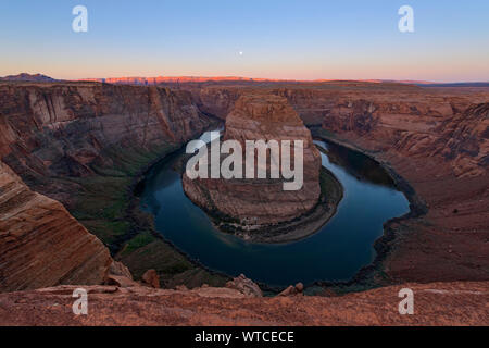Horseshoe Bend of the Colorado River with dawn light on distant Vermillion Cliffs, Page, Arizona, USA - Stock Photo