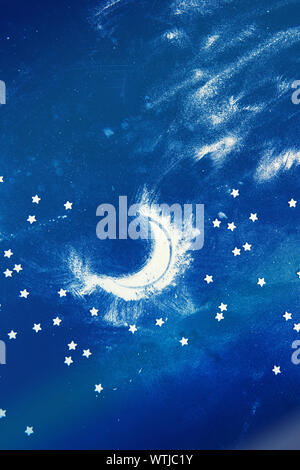 Night sky and moon: composition made of flour and candy stars on dark blue background. Vertical orientation - Stock Photo