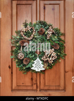 New Year and Christmas decor. Ornament a wreath from branches ate with cones, lights of a garland and gold spheres. Traditional Christmas decoration f - Stock Photo