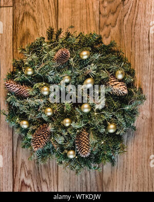 Christmas and New Year decor. Ornament a wreath from branches with cones, lights of a garland and gold spheres. Traditional Christmas decoration for i - Stock Photo
