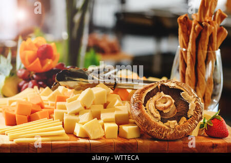 Rustic mix of cheese cuts, mushrooms and fruits on a wooden platter, during brunch buffet. Tasty assortment of fresh cheese selection, various types o - Stock Photo