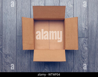 Flat lay of empty open cardboard box on wooden surface - Stock Photo