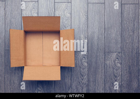Flat lay of empty open cardboard box on wooden surface with empty space - Stock Photo