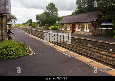 The railway station Horton-in-Ribblesdale, North Yorkshire on a dull, cloudy day, with a diesel passenger train approaching northbound in the distance - Stock Photo
