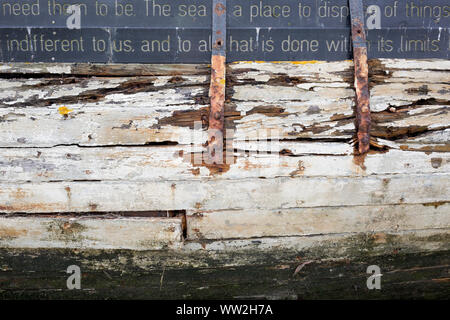 A detail of poetry and sentences forming 'Graveyard of Lost Species', a boat artwork created by by artists and commissioned by Arts Catalyst, at low-tide on the Thames estuary, at Leigh creek, on 10th September 2019, in Leigh-on-Sea, Essex, England. The project celebrates the local tradition of wrecking boats on the salt marsh, its decaying memory of what has changed or passed. The boat is the 'Souvenir', a 39-foot Thames 'bawley' (1933) which once served the local fish trade in nearby Southend-on-Sea. - Stock Photo