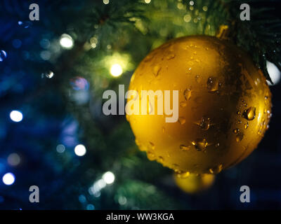 Golden globe hanged on Christmas fir tree in the city with lights defocused in background - Stock Photo