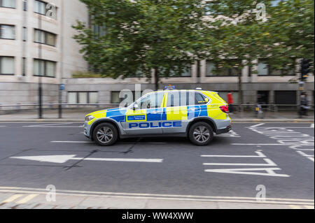 Metropolitan Police car travelling at speed with blue lights on in City of London, England, UK. - Stock Photo