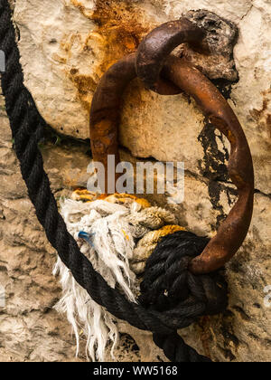 Worn rusty old mooring ring on harbour wall with attached ropes - Stock Photo