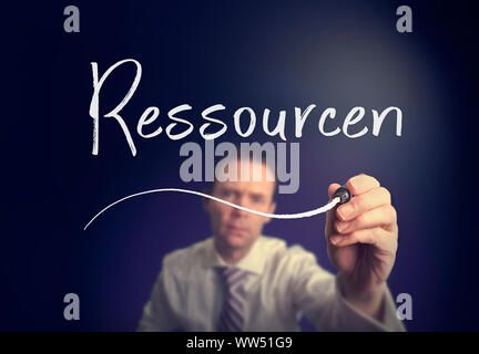 A businessman writing a Resources 'Ressourcen' concept in German with a white pen on a clear screen. - Stock Photo