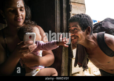 Three generations, young woman sitting with her baby and using her mobile phone, the grandfather making fun with the child on her arm - Stock Photo