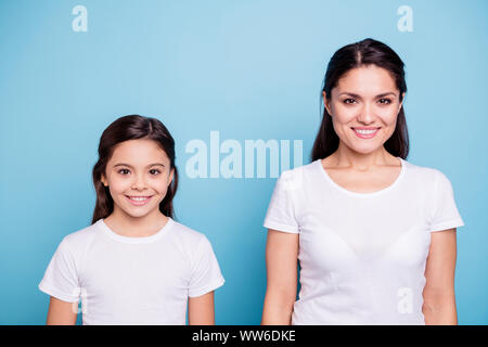 Close up photo two people brown haired mum and small daughter standing straight looking to camera wearing white t-shirts isolated on bright blue - Stock Photo