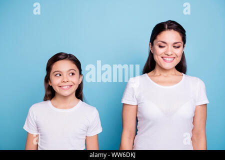Close up photo amazing pretty two people brown haired mum and small daughter standing straight looking side each other cunning wearing white t-shirts - Stock Photo