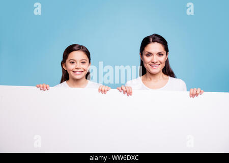 Close up photo pretty two people brown haired mum little daughter toothy beaming smile blank signboard poster in arms sale discount wearing white t - Stock Photo