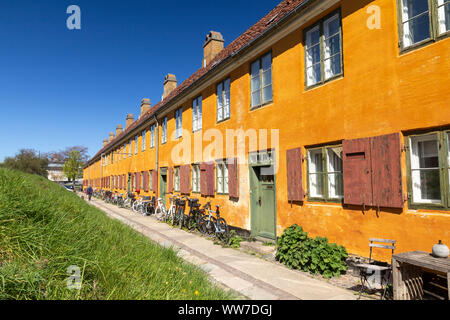 Historic row yellow houses in Nyboder neighborhood in Copenhagen, a former Naval district with bikes in front of the houses - Stock Photo