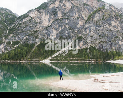 Autumn hike around the Pragser Wildsee in the Dolomites, Italy, man standing on the shore and looking over the lake - Stock Photo