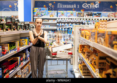 KYIV- JAN 6, 2019: Mother with her little son in kids store buy cars. - Stock Photo