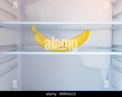 One yellow sad banana in open empty refrigerator with frozen ice on the wall. Weight loss diet and hunger concept. - Stock Photo