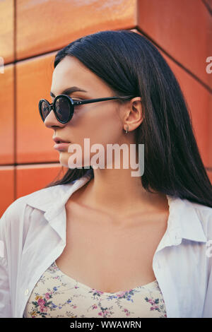 Close-up portrait of an attractive young brunette woman in dark sunglasses posing in a city and looking away, against an orange building, sunny summer - Stock Photo