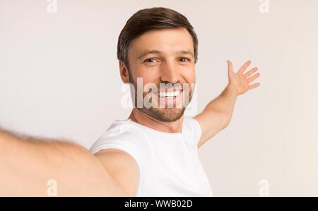 Man Taking Selfie Showing Something Behind Him, White Background - Stock Photo