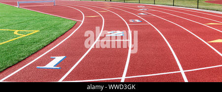 Landscape view of a red track with white numbers that have blue trim at the two hundred meter start. - Stock Photo