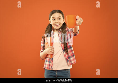 Help yourself. Cute schoolgirl enjoying school break on orange background. Little girl having tea break. Small child holding book and cup at meal break. Its break time. - Stock Photo