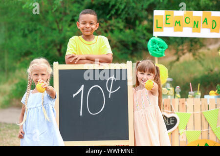 Cute little children selling lemonade in park - Stock Photo