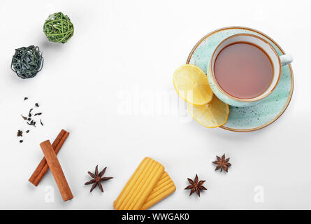 Cup of tasty tea with spices and cookies on white background - Stock Photo