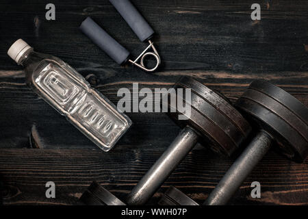 Fitness workout equipment. Dumbbell or barbell on a wooden floor desk surface. Flat lay desaturated concept - Stock Photo