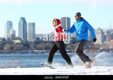 Happy couple snowshoeing running in montreal with cityscape skyline and river st. Lawrence in background. Healthy lifestyle photo from Montreal, Quebe - Stock Photo