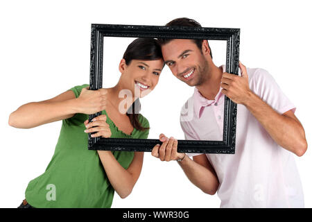 Couple holding empty art frame - Stock Photo