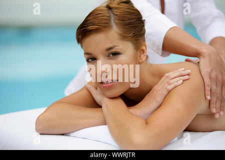 Woman receiving back massage by the pool - Stock Photo