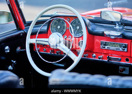 Nuremberg, Germany - September 15, 2019: Detail with the steering wheel and the dashboard of a red colored Mercedes-Benz 190 SL Cabrio vintage car - Stock Photo